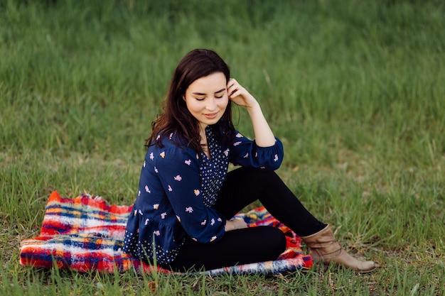Joven hermosa niña sentada sobre una tela escocesa en el parque de la primavera