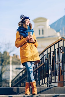 Joven hermosa niña sonriente en un gorro y bufanda con termo taza en manos de la ciudad