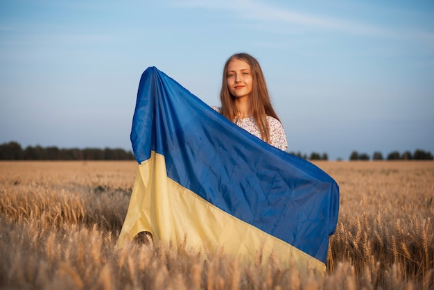 Joven hermosa niña ucraniana sonriente con bandera nacional en campo de centeno