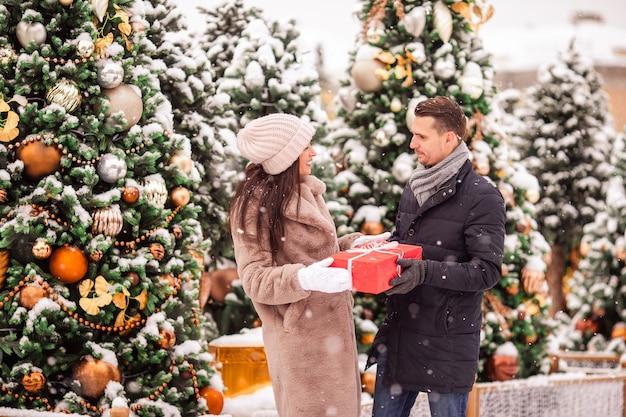Joven hermosa pareja alegre celebrando la navidad en la calle de la ciudad y regalar el uno al otro.