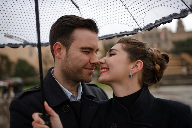 Joven hermosa pareja amorosa hispana camina bajo un paraguas durante la lluvia en la plaza españa. pareja posando en el contexto del museo nacional de arte de cataluña.