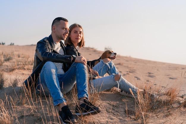 Joven hermosa pareja caucásica vistiendo chaqueta de cuero y jeans camina arena del desierto con el mejor amigo del perro beagle. familia con perro sin hijos descansando en la naturaleza. emociones positivas personas felices