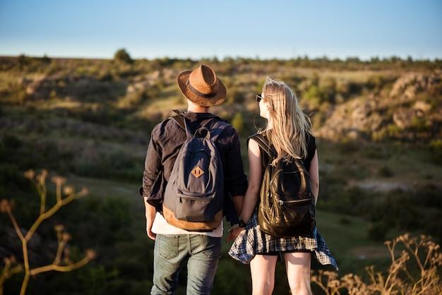 Joven hermosa pareja descansando, disfrutando de la vista en el cañón