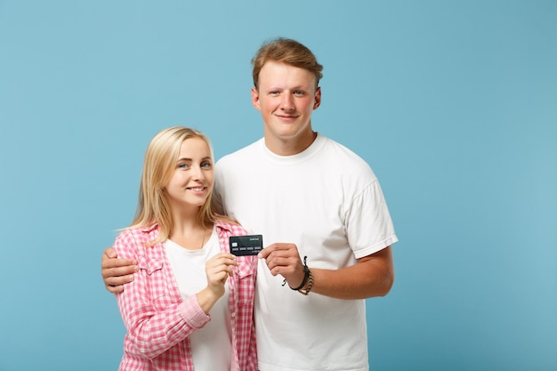 Joven hermosa pareja dos amigos chico y mujer en blanco rosa camisetas en blanco vacías posando