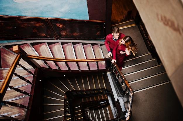 Joven hermosa pareja elegante en un vestido rojo en grandes escaleras vintage de madera