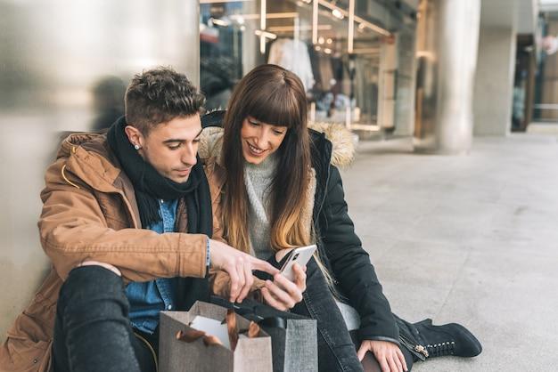 Joven hermosa pareja enamorada de compras por la calle tomando un descanso para sentarse en el piso de compras en el teléfono móvil