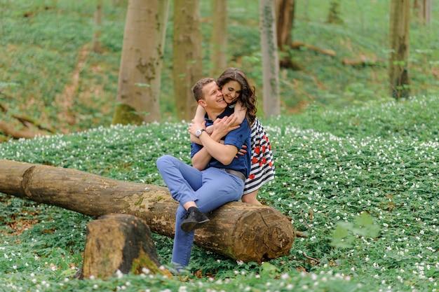Joven hermosa pareja de enamorados en el bosque. un hombre se sienta en un árbol talado. una mujer lo abraza por detrás. espacio libre.