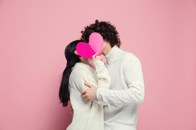 Joven, hermosa pareja de enamorados en la pared rosada del estudio