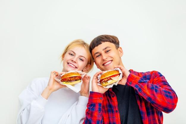 Joven hermosa pareja feliz chico y chica comiendo grandes deliciosas hamburguesas sobre fondo blanco.