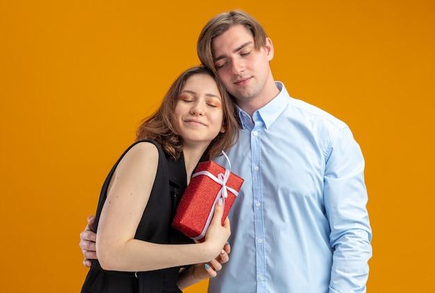 Joven hermosa pareja feliz hombre y mujer con presente en manos sonriendo alegremente abrazando felices enamorados juntos celebrando el día de san valentín de pie sobre la pared naranja