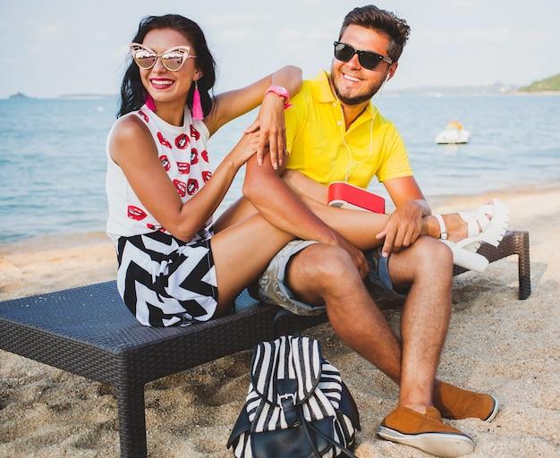 Joven hermosa pareja hipster enamorada sentada en la playa, escuchando música, gafas de sol, atuendo elegante, vacaciones de verano, divirtiéndose, sonriendo, feliz, colorido, emoción positiva