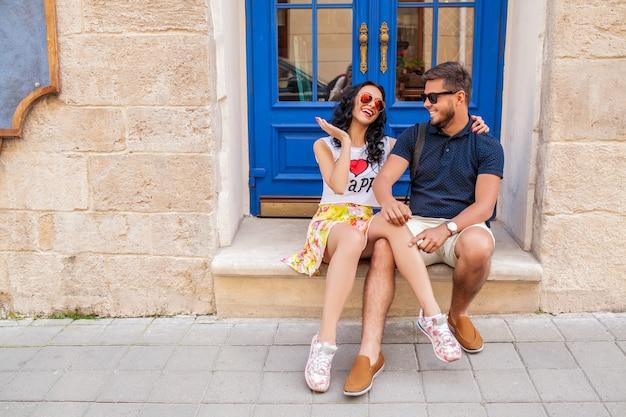 Joven hermosa pareja de hipster enamorados sentados en la calle de la ciudad vieja