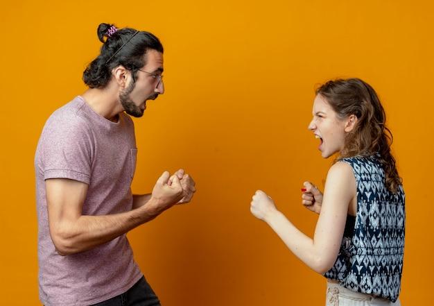 Joven hermosa pareja de hombres y mujeres peleando y gesticulando tener una pelea loca y frustrada de pie sobre la pared naranja