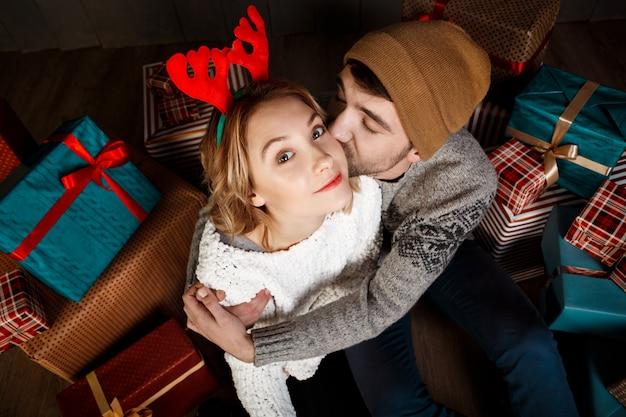 Joven hermosa pareja sonriente abrazando sentado entre cajas de regalo de navidad.