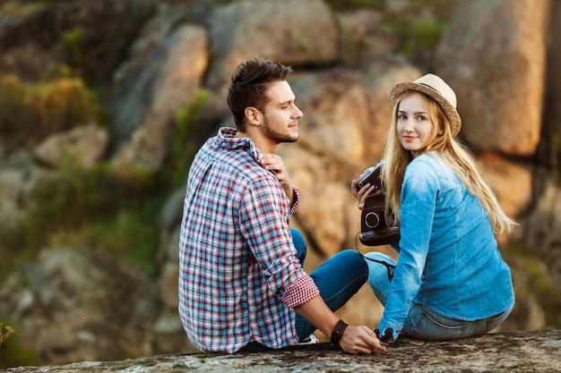Joven hermosa pareja de viajeros disfrutando de la vista del cañón, sonriendo