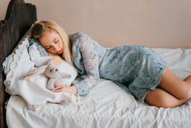 Joven hermosa rubia adolescente durmiendo en la cama de madera vintage con juguete.