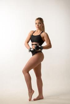Joven hermosa rubia sexy boxeo chica posando con guantes en la pared blanca