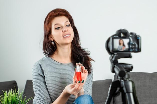 Una joven hermosa está sentada frente a una dslr y graba un vlog, primer plano