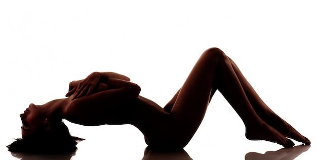 Joven hermosa silueta de mujer completamente desnuda acostada sobre fondo blanco