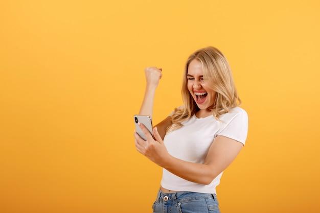 Joven, hermosa y sonriente niña mira el teléfono y hace un gesto ganador