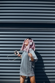 La joven hermosa usa un teléfono inteligente en la calle, navega por internet y escucha música.
