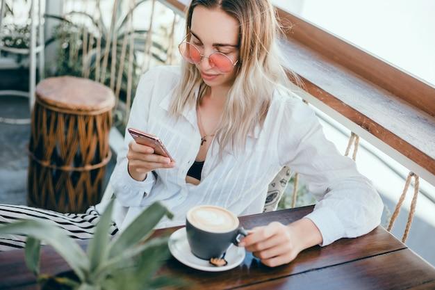 Joven hermosa usa un teléfono inteligente en la calle, navegando por internet