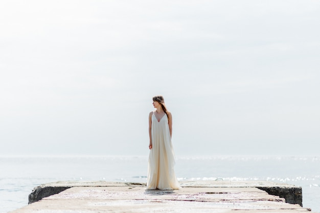 Una joven hermosa con un vestido largo y blanco camina por la playa y el muelle contra el mar.