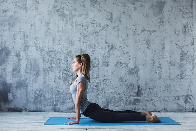 Joven hermosa yoga posando en gris