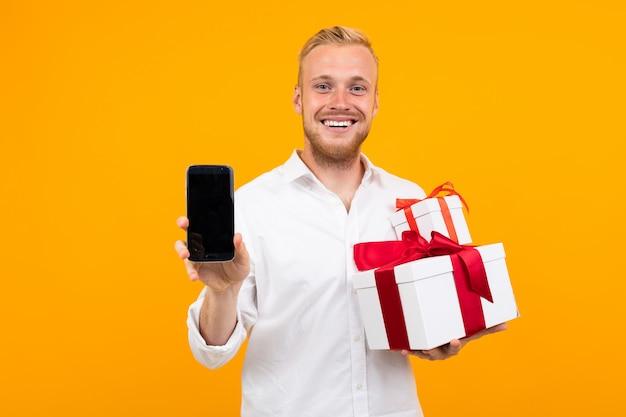 Joven hermoso con cabello rubio en camisa blanca tiene caja blanca con regalo y llamar al teléfono aislado en amarillo