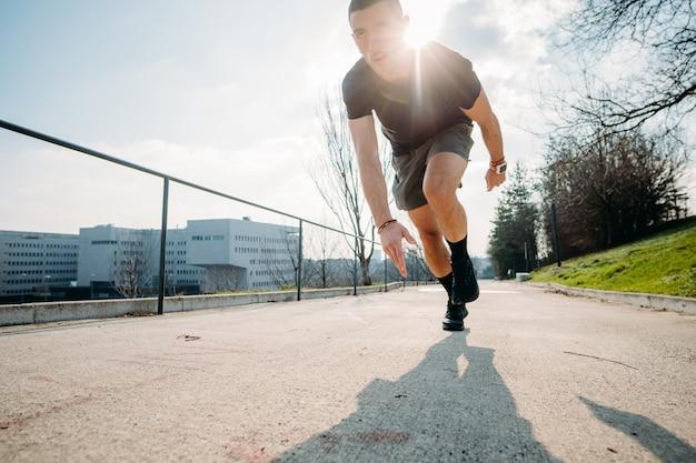 Joven hermoso entrenamiento al aire libre corriendo al aire libre