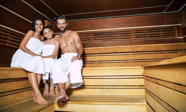 Joven hermoso feliz padre y madre con pequeña hija linda en las toallas de baño se están relajando en la sauna caliente