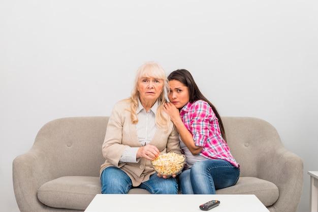 Joven hija viendo la película de terror con su madre senior sosteniendo un tazón de palomitas de maíz