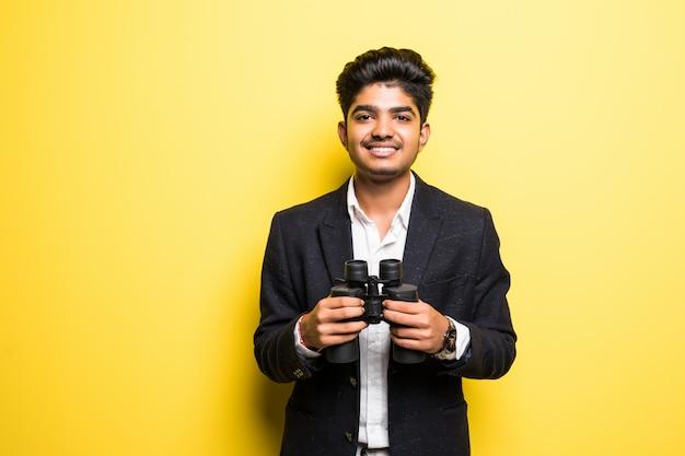 Joven hindú con binoculares aislados en pared amarilla