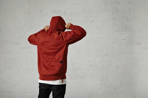 Un joven hipster ajusta la capucha de su parka rojo pardusco, vista posterior, retrato en estudio con paredes blancas