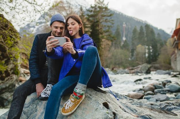 Joven hipster hermosa pareja de enamorados sosteniendo smartphone, tomando fotografías, sentado sobre una roca en el río en el bosque de invierno