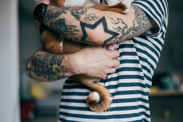 Joven hipster de moda con tatuajes loco pelo rizado abraza a su pequeño mejor amigo