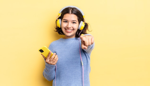 Joven hispana apuntando a la cámara eligiéndote. concepto de auriculares y teléfono inteligente