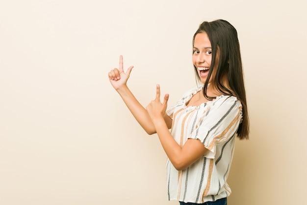 Joven hispana apuntando con los dedos índices a un espacio de copia, expresando entusiasmo y deseo.