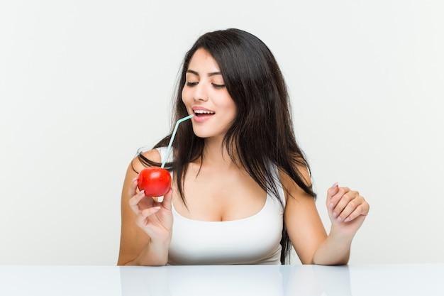Joven hispana bebiendo un jugo de tomate con una pajita