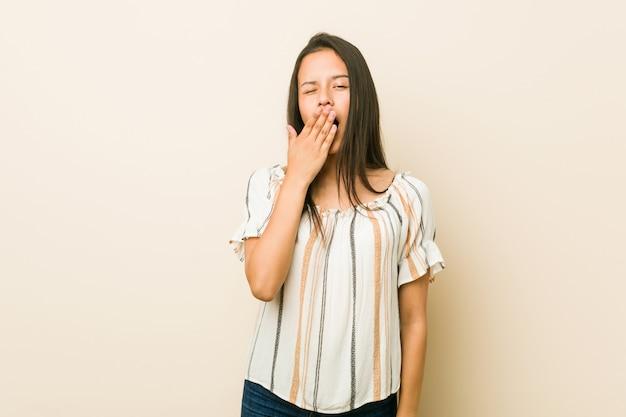Joven hispana bostezando mostrando un gesto cansado cubriendo la boca con la mano.