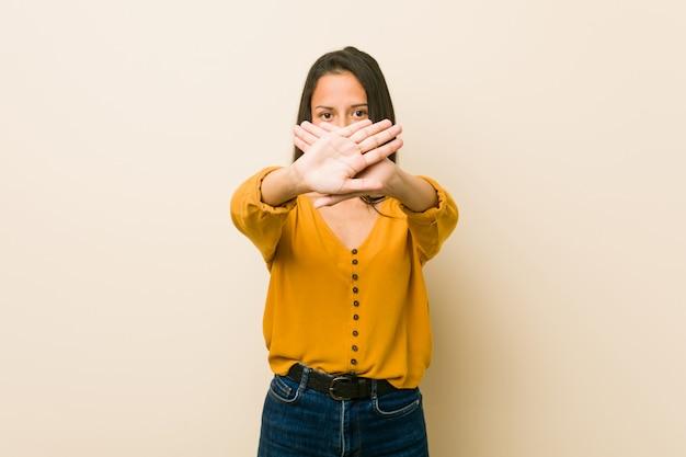 Joven hispana contra una pared beige haciendo un gesto de negación
