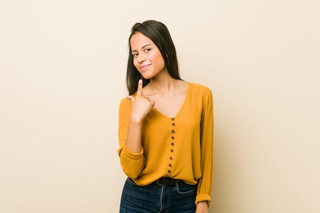 Joven hispana contra una pared de color beige apuntando con el dedo hacia ti como si invitara a acercarse.
