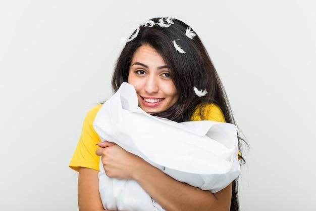 Joven hispana despertando y sosteniendo una almohada