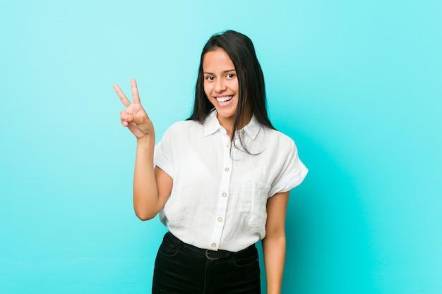 Joven hispana fresca contra una pared azul alegre y despreocupada mostrando un símbolo de paz con los dedos.