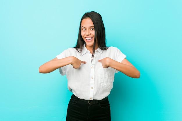 Joven hispana fresca contra una pared azul sorprendida señalando con el dedo, sonriendo ampliamente.