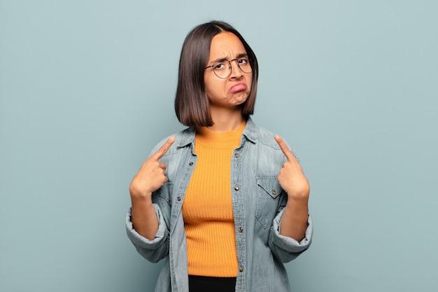 Joven hispana con mala actitud luciendo orgullosa y agresiva, apuntando hacia arriba o haciendo letreros divertidos con las manos