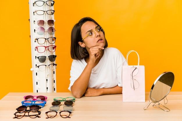 Joven hispana probándose gafas aisladas mirando hacia los lados con expresión dudosa y escéptica.