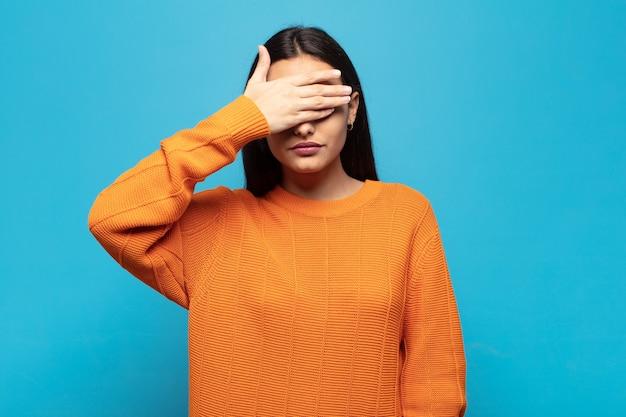 Joven hispana que cubre los ojos con una mano sintiéndose asustada o ansiosa