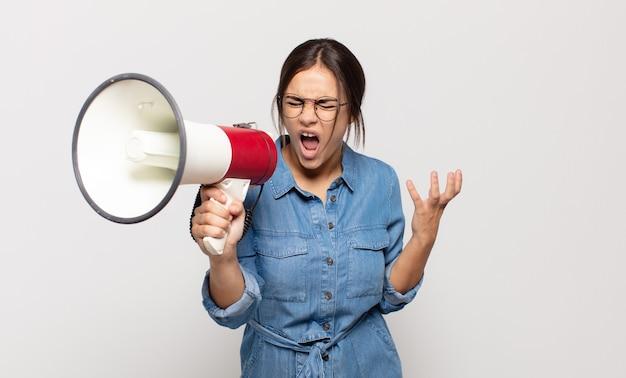 Joven hispana que parece enojada, molesta y frustrada gritando wtf o qué te pasa