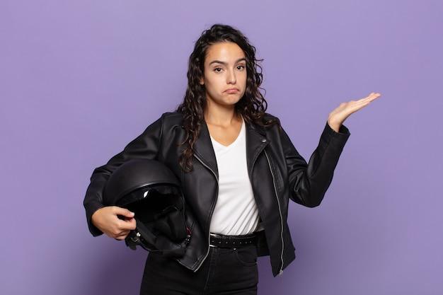 Joven hispana que se siente desconcertada y confundida, dudando, ponderando o eligiendo diferentes opciones con expresión divertida